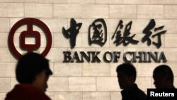 Люди проходят мимо штаб-квартиры Банка Китая в Пекине. 25 октября 2012 года.