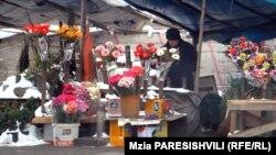 Вокруг строительного забора под открытым небом вот уже четыре года ютятся продавцы цветов. Им обещают, что в этом строящемся павильоне им выделят площади для небольших магазинчиков