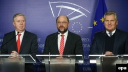 Former European Parliament President Pat Cox (left), former Polish President Aleksander Kwasniewski (center), and European Parliament President Martin Schulz address a press conference at the European Parliament in Brussels on December 4.