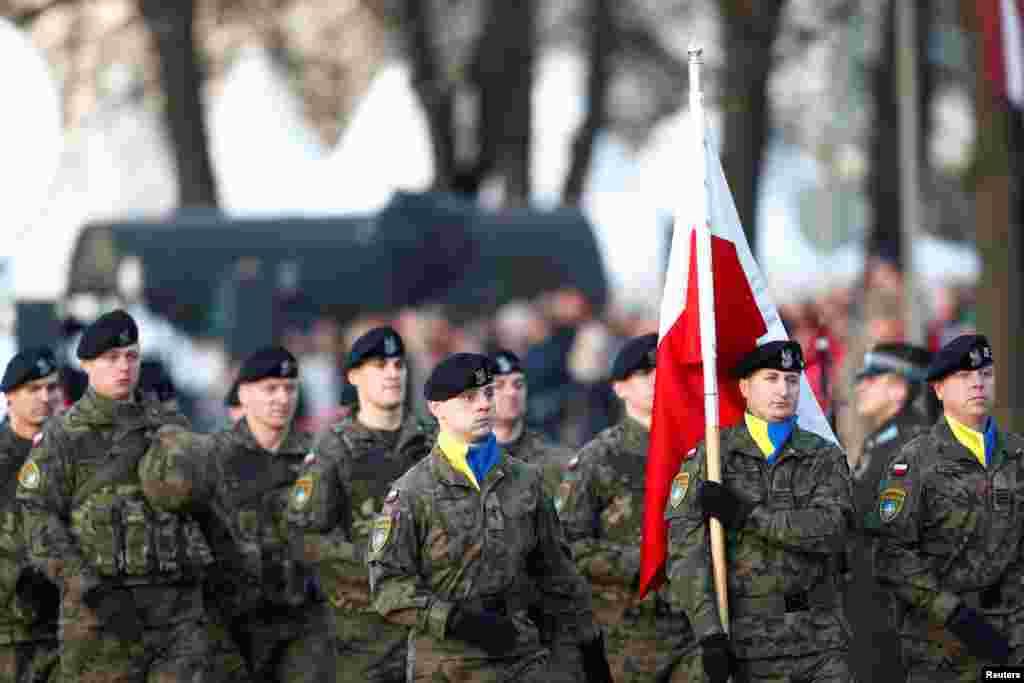 Польські військові у жовто-блактиних хустках несуть прапор Польщі