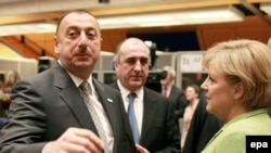 The president of Azerbaijan, Ilham Aliyev (left) chats with German Chancellor Angela Merkel (right) in Prague