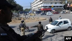 Policemen stand guard at a security checkpoint in Karachi.