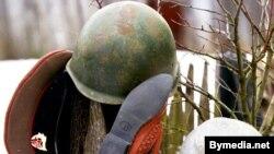 Belarus -- Soldier's peak-cap, soldier's helmet, bedroom-slippers and pig-iron pot on a fence, Apr1999