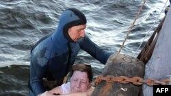 Водолаз достает из воды тело одной из жертв кораблекрушения