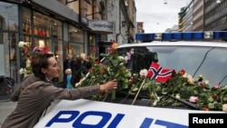 A woman places flowers on a police vehicle after a memorial march to mourn for the victims of the killing spree and bomb blast in Oslo on July 25.