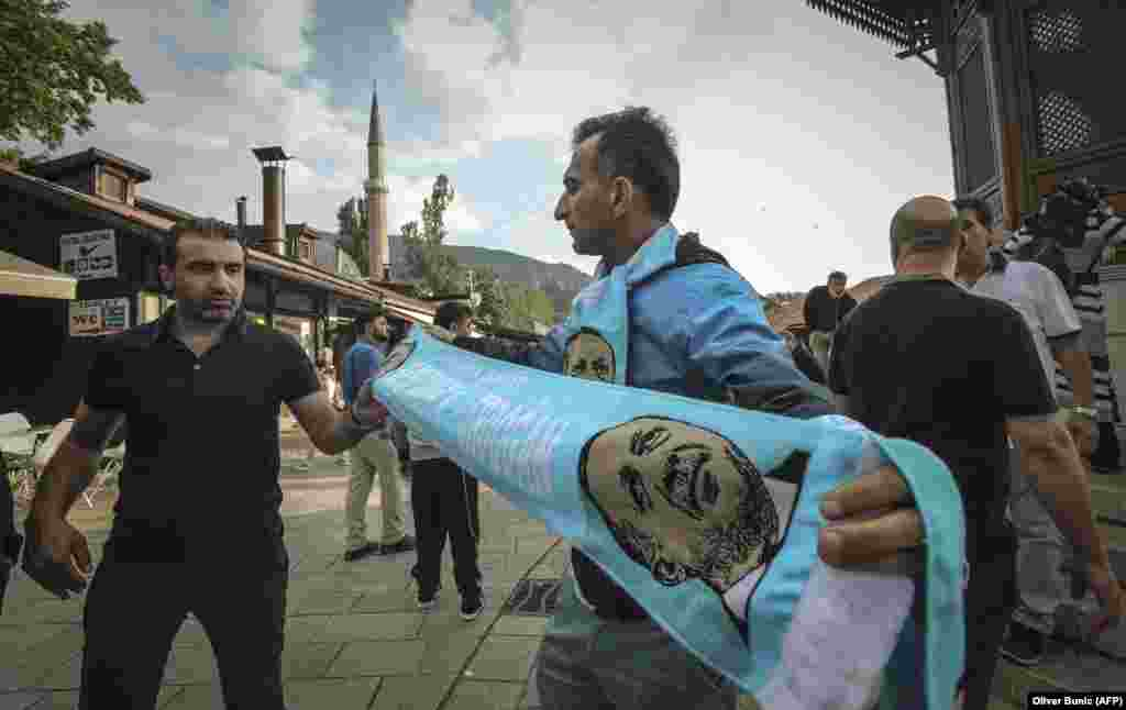 A man sells a scarf with an image of Turkish President Recep Tayyip Erdogan at the Bascarsija main square in Sarajevo on May 19, ahead of his visit for a campaign rally the next day. (AFP/Oliver Bunic)