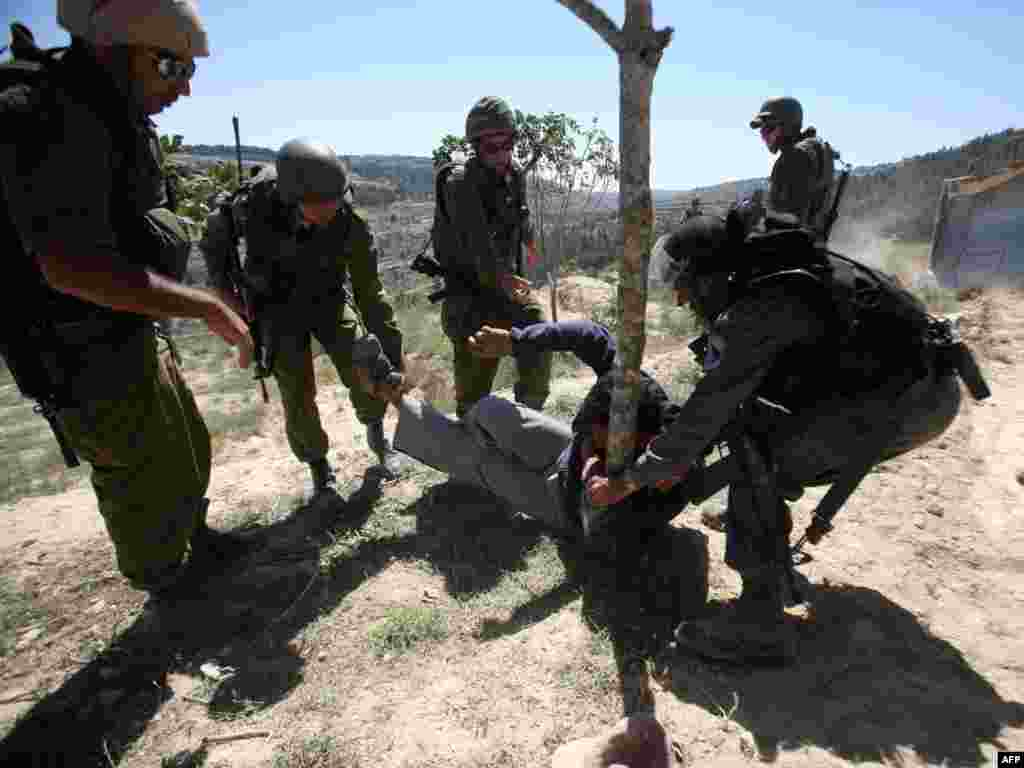 Ізраільскія вайскоўцы прыбіраюць палестынца з трасы бульдозэра на Заходнім Беразе Ярдану