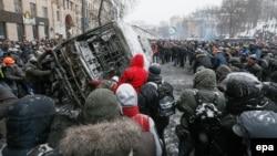 Протестующие опрокидывают сгоревший автобус, принадлежащий МВД. Киев, 21 января 2014 года.