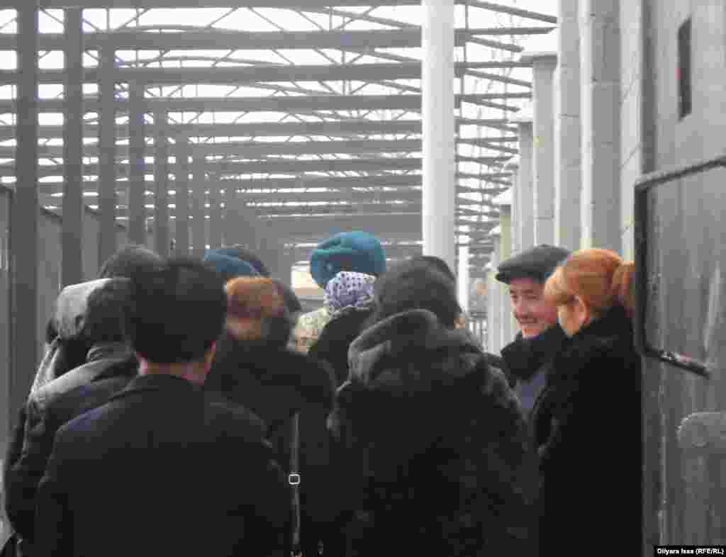 Очередь желающих пересечь границу Казахстана, чтобы попасть в Узбекистан. Каждый проходящий границу на таможенном посту проходит через паспортный контроль и электронный сканер.