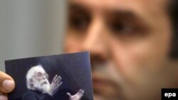Rasim Ljajić, predsednik Nacionalnog saveta za saradnju sa Haškim tribunalom, drži fotografiju na kojoj je Radovan Karadžić