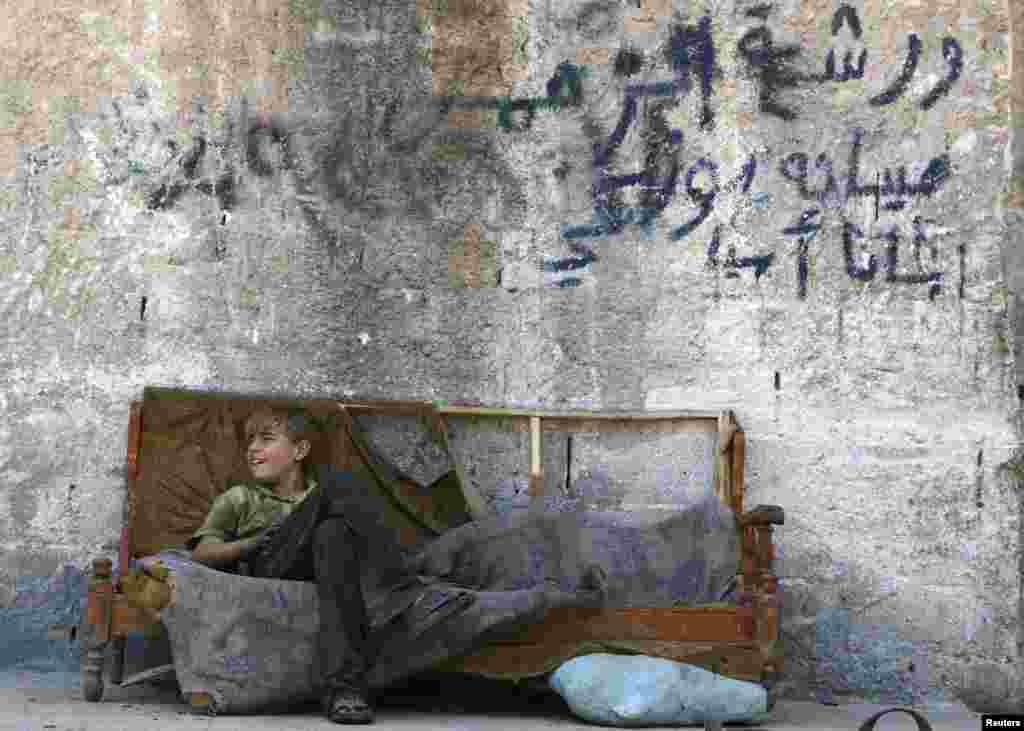 A boy sits on a sofa along a street in the Al-Fardus neighborhood of the devastated Syrian city of Aleppo. (Reuters/Hosam Katan)