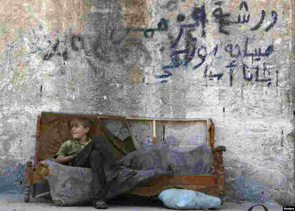 A boy sits on a sofa along a street in the Al-Fardus neighborhood of the devastated Syrian city of Aleppo. (Reuters/Hosam Katan)