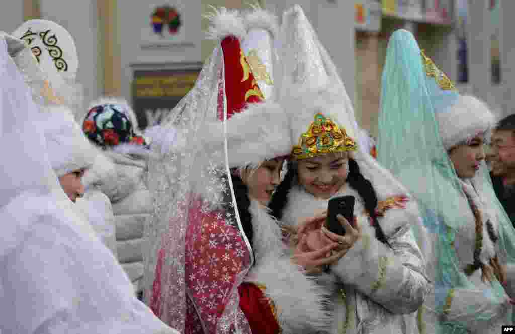 "Women dressed as ""Snegurochka"" (Snow Maiden) look at a mobile phone during the New Year's parade in the Kyrgyz capital, Bishkek, on December 31. (AFP/Vyacheslav Oseledko)"