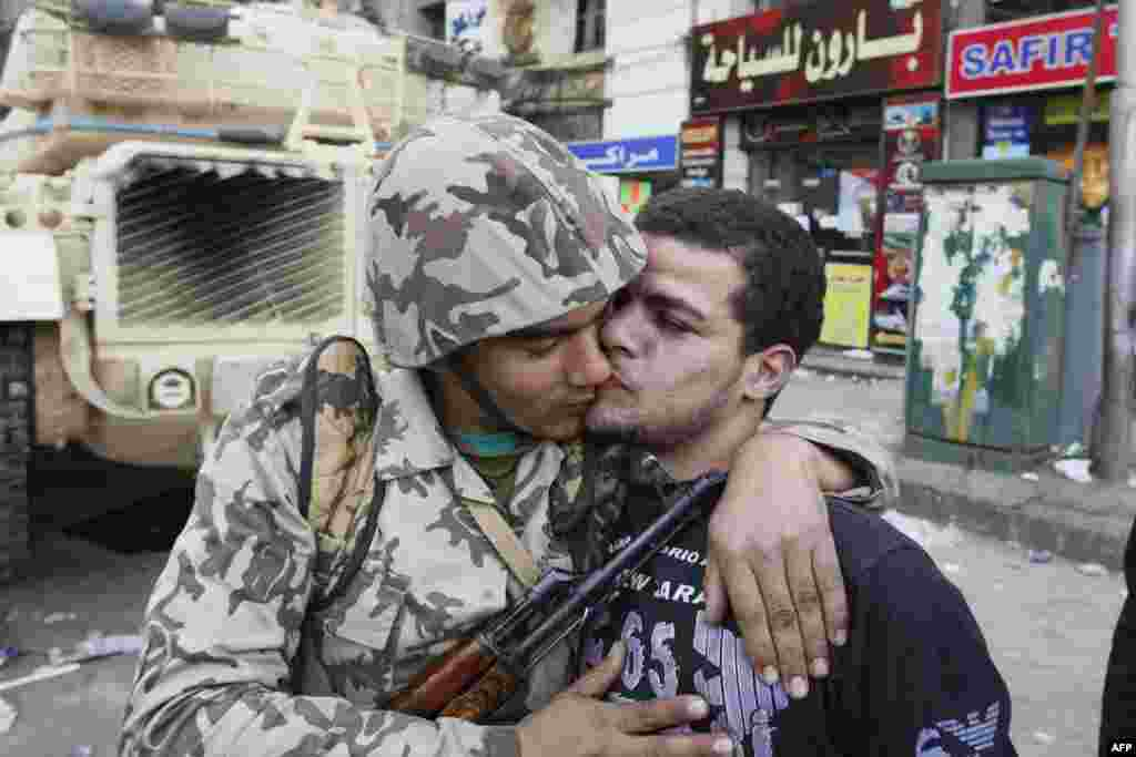 An Egyptian civilian kisses an army soldier after troops took position at major junctions in central Cairo on January 29, 2011.