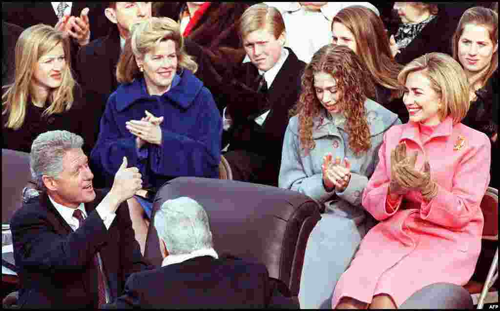 U.S. President Bill Clinton gives a thumbs up to Hillary Clinton and their daughter, Chelsea, after being sworn in for his second term as president on January 20, 1997.