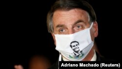Președintele Braziliei Jair Bolsonaro purtând o mască cu propria sa imagine.