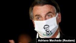 Žair Bolsonaro na konferenciji za medije sa maskom na kojoj je njegov lik, Brazil, 22. maj 2020.