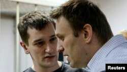 Russian opposition leader and anticorruption blogger Aleksei Navalny (front) and his brother and co-defendant Oleg attend a court hearing in Moscow in December 2014.