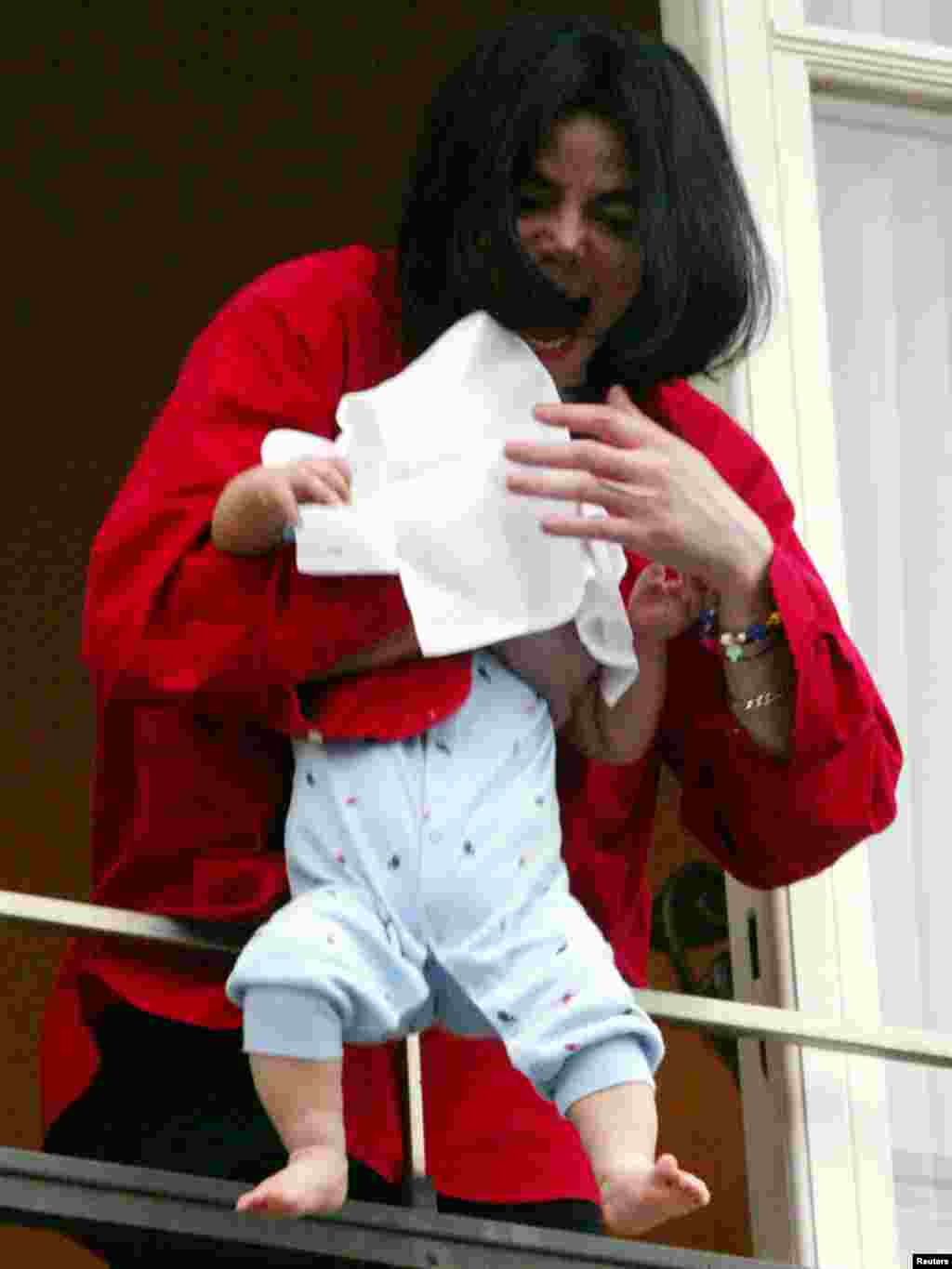 Entertainer and popstar Michael Jackson holds an unidentified child, covered with a towel, as he looks down to fans out of a window after he arrived at a Berlin hotel November 19, 2002. Michael Jackson was in Berlin to be awarded with the prestigious Bambi 2002 media award for his lifetime achievement. REUTERS/Tobias Schwarz