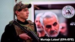 یکی از اعضای حشد الشعبی عراق در کنار تصویری از قاسم سلیمانی