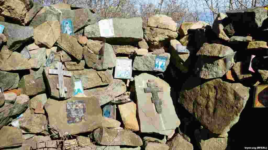 Паломники оставляют среди камней кресты и иконы