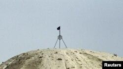 Флаг группировки «Исламское государство» на холме в городе Тель-Абьяд на сирийско-турецкой границе, сентябрь 2014 года