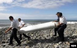 Офицерлер Францияның Ла Реюнион аралы мағынан табылған белгісіз ұшақтың сынықтарын көтеріп барады. 29 шілде 2015 жыл.