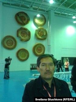 Художник Арыстанбек Шалбаев на фоне своей инсталляции «7 дней». Астана, 12 октября 2012 года.