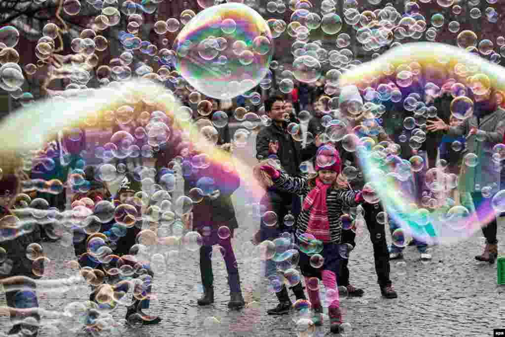 Visitors and children play with big and small bubbles in Cologne, Germany. (epa/Maja Hitij)