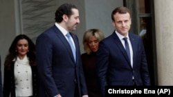 Lebanon's Prime Minister Saad Hariri (center) and his wife, Lara (left), leave after a lunch with French President Emmanuel Macron (right) and his wife, Brigitte (second from right), at the Elysee Palace in Paris on November 18.