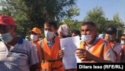 Протестующий показывает коллективное обращение с требованиями рабочих. Шымкент, 8 июля 2021 года