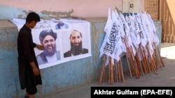 Afg'onistonlik yigit Tolibon oliy qo'mondoni Mulla Haybatutlloh Oxundzoda posteri va Tolibon bayroqlarini sotmoqda - Kobul, 24 - avgust, 2021