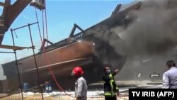 Firefighters combat a blaze at the Delvar Kashti Bushehr boat factory in the Iranian city of Bushehr on July 15.