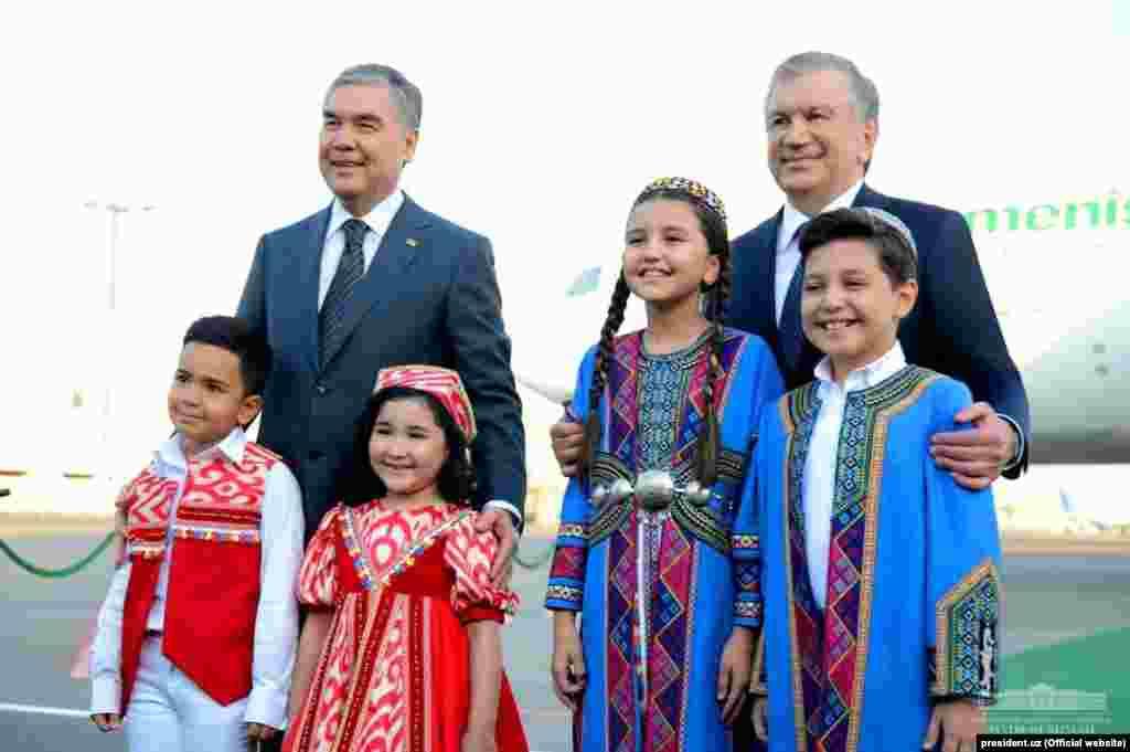 Özbek we türkmen prezidentleri Daşkendiň aeroportynda milli lybasdaky çagalar bilen surata düşýärler.