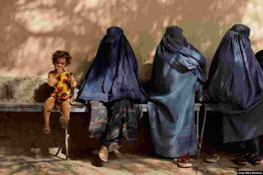 Një vajzë e vogël qëndron e ulur pranë disa grave me burka që gjenden pranë një spitali në Kabul të Afganistanit.