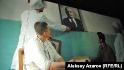 Кадра из фильма «Семь нот моего детства» (снято с киноэкрана): портрет одного вождя меняют на портрет другого вождя.