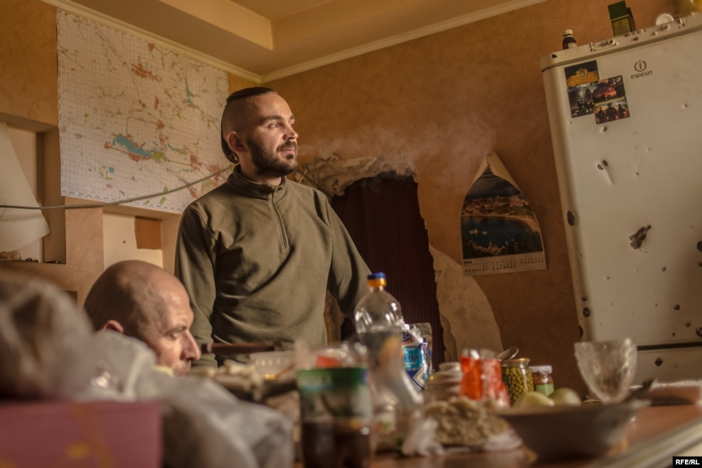 "A soldier who goes by the nom de guerre ""Nestor"" stands in the kitchen. A native of Russia, Nestor's decision to fight on the Ukrainian side may be unusual, but is not unheard of."
