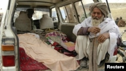 An elderly man sits next to the covered bodies of Afghans killed after what is believed to have been a shooting rampage by a U.S. soldier in Kandahar Province on March 11.