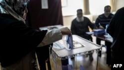 A woman casts her ballot in Istanbul as electoral workers look on in Turkish local elections on March 30.