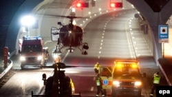 Rescuers work at the entrance to the tunnel in Switzerland, where the fatal crash occurred.