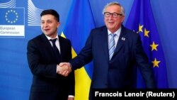 Ukrainian President Volodymyr Zelenskiy poses with European Commission President Jean-Claude Juncker at the EU Commission headquarters in Brussels on June 4.