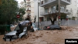 Архивска фотографија. Грција - Жена заглавена во нејзиниот автомобил е за време на поројниот дожд