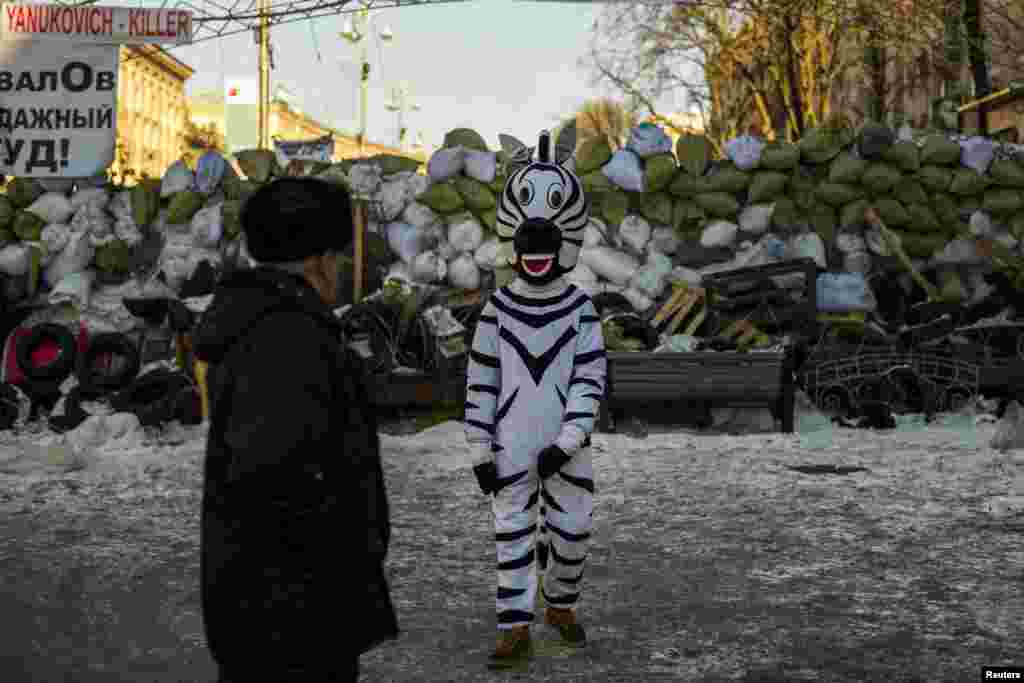 A man in a zebra costume invites passersby to have a picture taken in exchange for money outside a barricade on Independence Square in Kyiv, hub of two months of antigovernment protests. (Reuters/Thomas Peter)