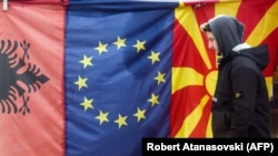 A man walks by Albanian EU, and Macedonian flags displayed in a bazaar in Skopje.
