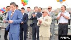 Бергей Рысқалиев (алдыңғы қатардағы көк киімді адам) Атырау облысы әкімі кезінде жаңа көпірдің ашылу салтанатында сөйлеп тұр. Атырау қаласы, 22 шілде 2009 жыл.
