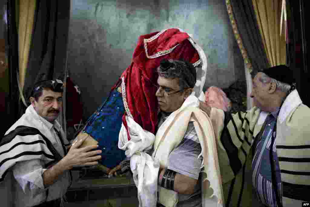 Iranian Jews carry a Torah scroll out from a cupboard to be read during morning prayers.