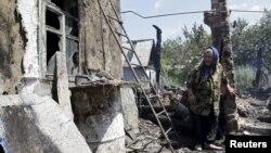 Жінка біля зруйнованого будинку на Донеччині (ілюстраційне фото)