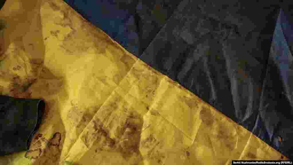 Флаг, которым были накрыты погибшие украинские военные во время транспортировки. Воины погибли 13 августа 2014 в поселке Новосветловка Луганской области. Ими были накрыты бойцы первого механизированного батальона 24-й отдельной механизированной бригады капитан Виталий Бондаренко, лейтенанты Владислав Рыльский и Юрий Думанский, солдат Михаил Романович. Флаг в музей передал отец Владислава Рыльского