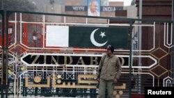 Një ushtar pakistanez para një pike të përbashkët kontrolli me Indinë