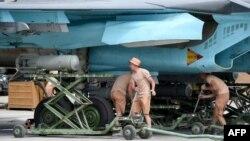 Российские военные закрепляют бомбы на военном самолете Су-34 на авиабазе Хмеймим в Сирии. 4 мая 2016 года.